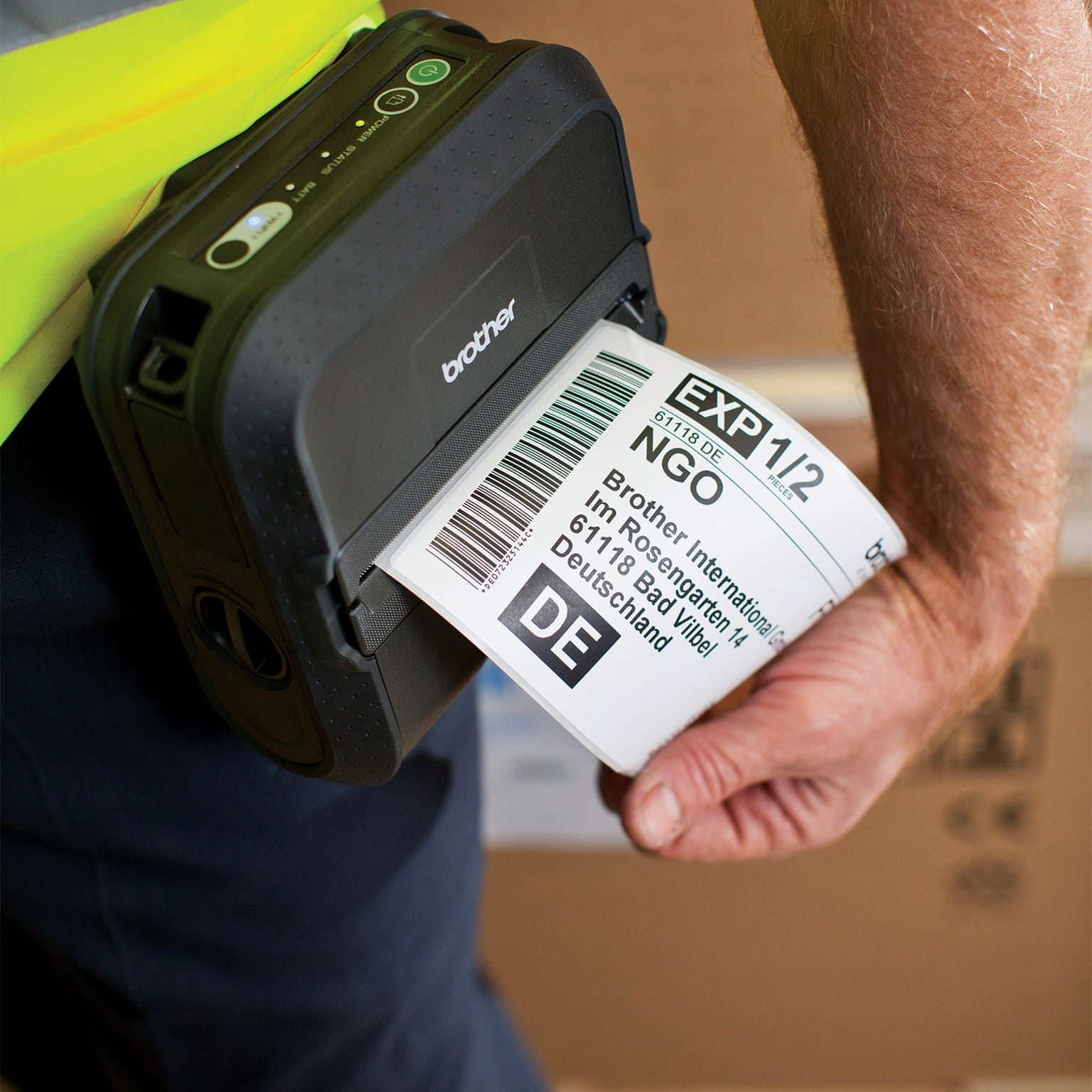 A Brother portable label printer being used by warehouse staff to print labels for packaging