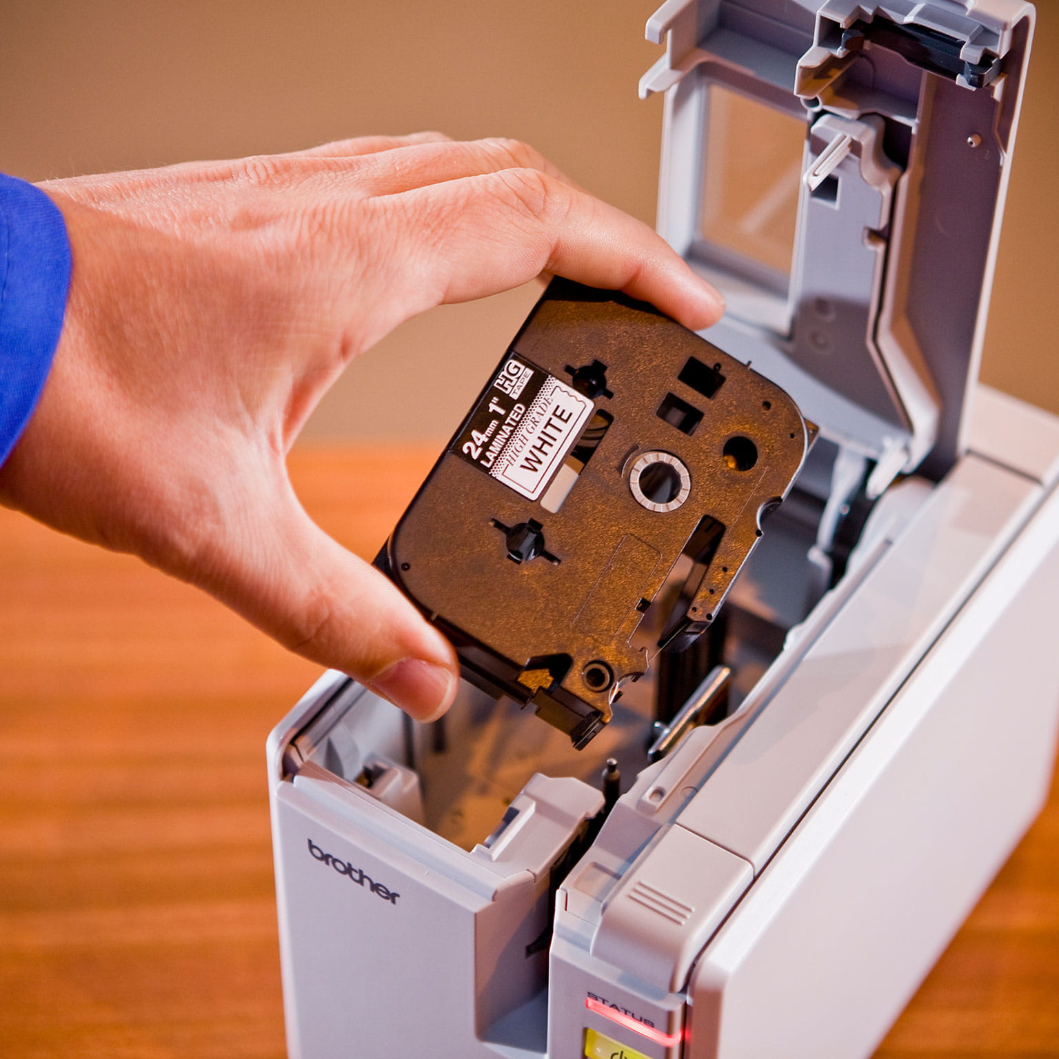 A Brother customer replacing a cartridge on a desktop label printer