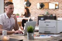 Man sat at desk with multifunction printer on desk
