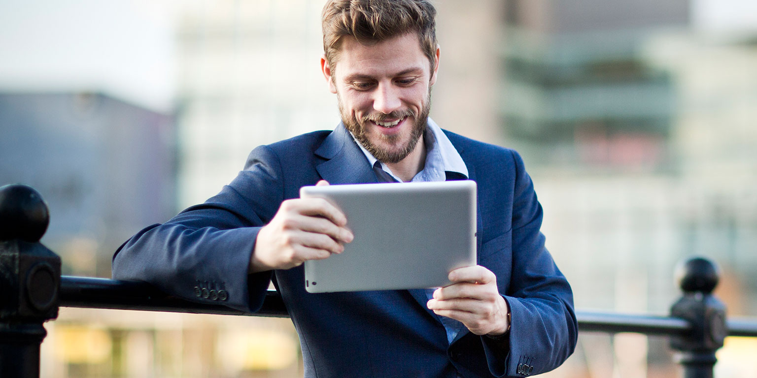 Business man sat outside reading the Brother blog on his tablet
