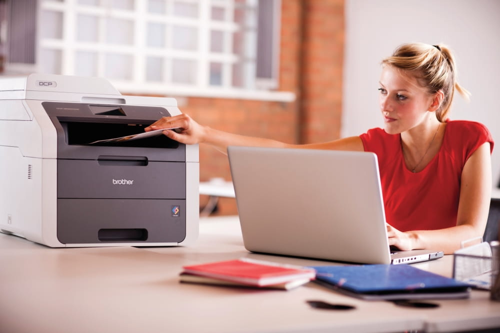 Office worker sat at desk discusses the benefits of managed print services