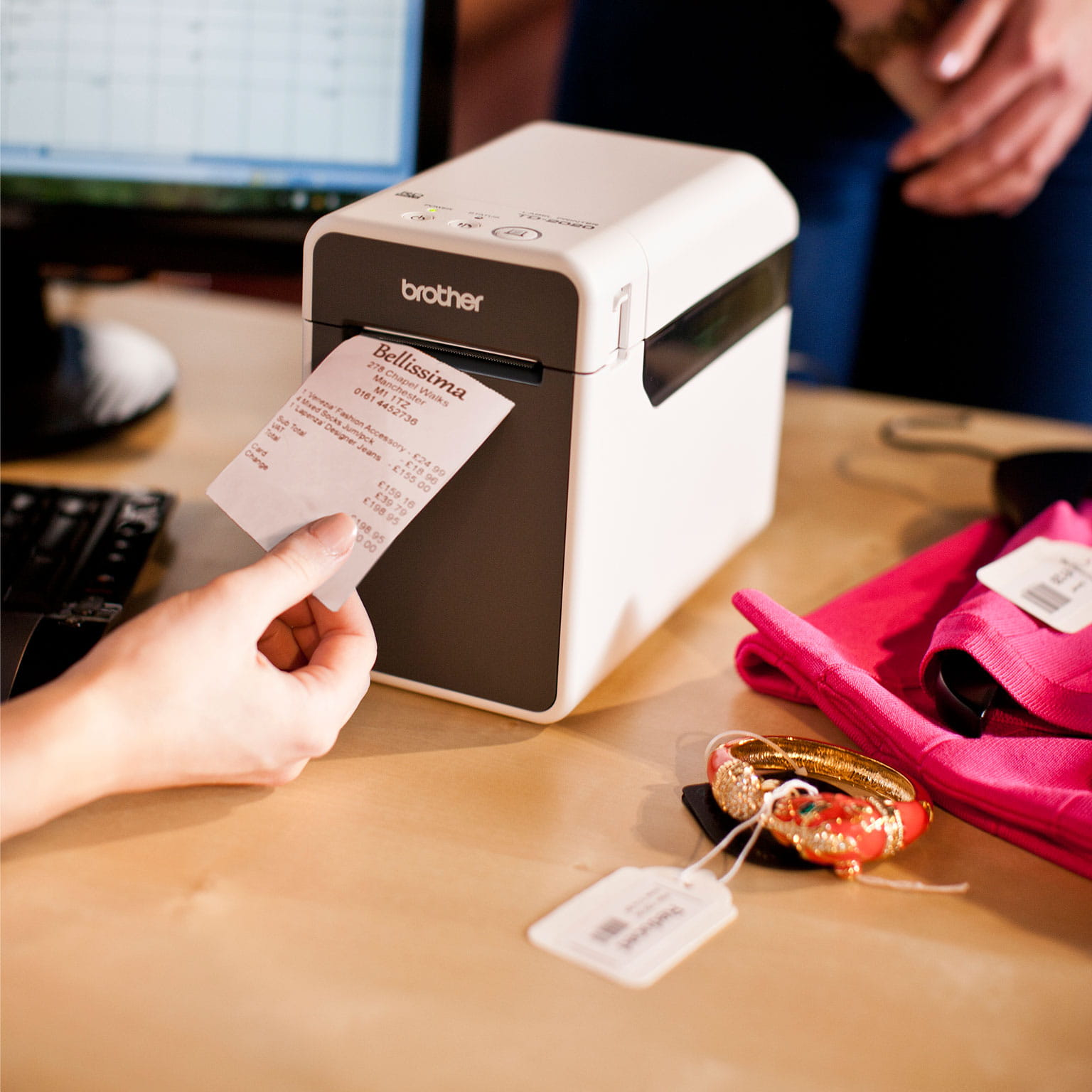 A Brother portable label printer being used by shop assistant to print price labels in a clothes shop