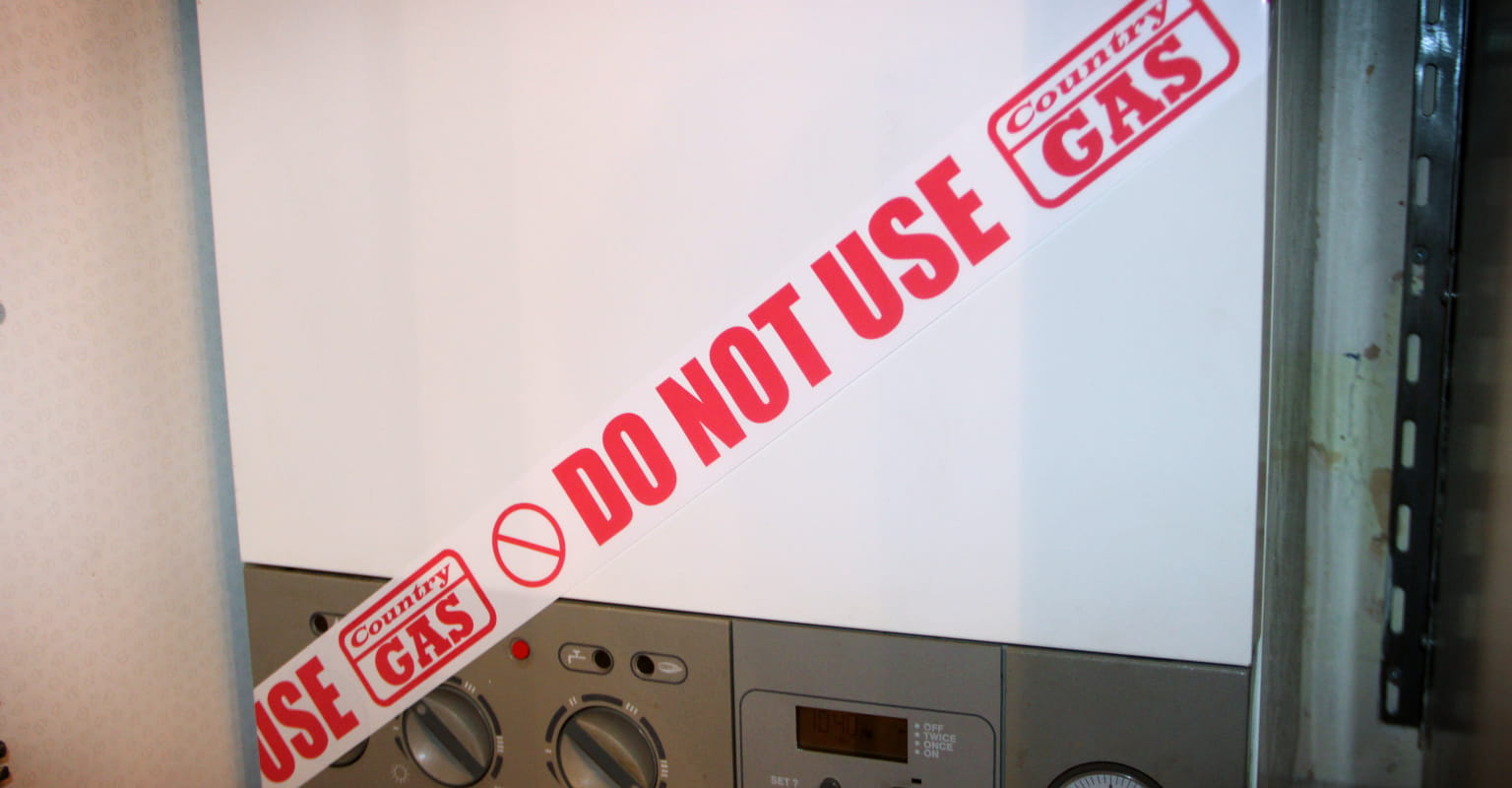"""Customised adhesive roll wrapped around a faulty gas boiler stating """"Do not use"""""""