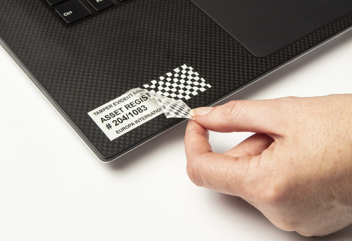 Person removing a tamper evident security tape off a laptop, leaving a checkerboard pattern