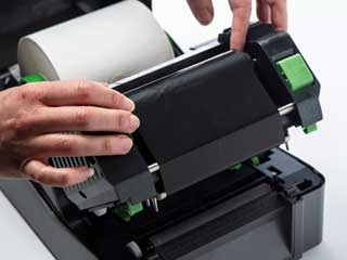 Thermal transfer ink ribbon being installed in a TD-4D label printer