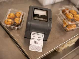 Brother TD-4D label printer on steel table next to cakes in a bakery