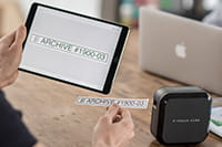 Person uses a tablet to print labels to the P-touch CUBE Plus label printer using wireless bluetooth connection