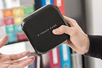 The compact Brother P-touch CUBE Plus label printer being handed over between users