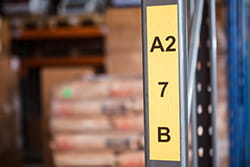 Yellow printed label affixed to metal shelving unit in a warehouse