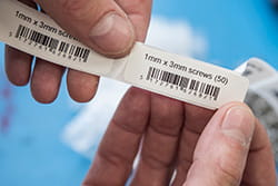 Person holding printed labels showing product information and barcodes