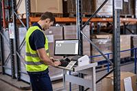 Man wearing hi-vis printing in warehouse using Brother TD-4420DN desktop label printer