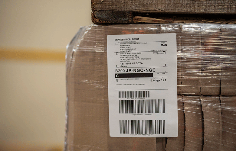 Close up of white shipping label on wrapped brown box
