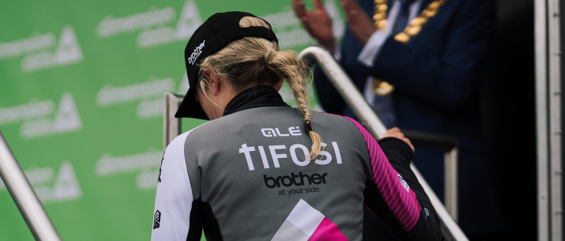 The back of cyclist Leah Dixon while she's climbing steps up to a podium