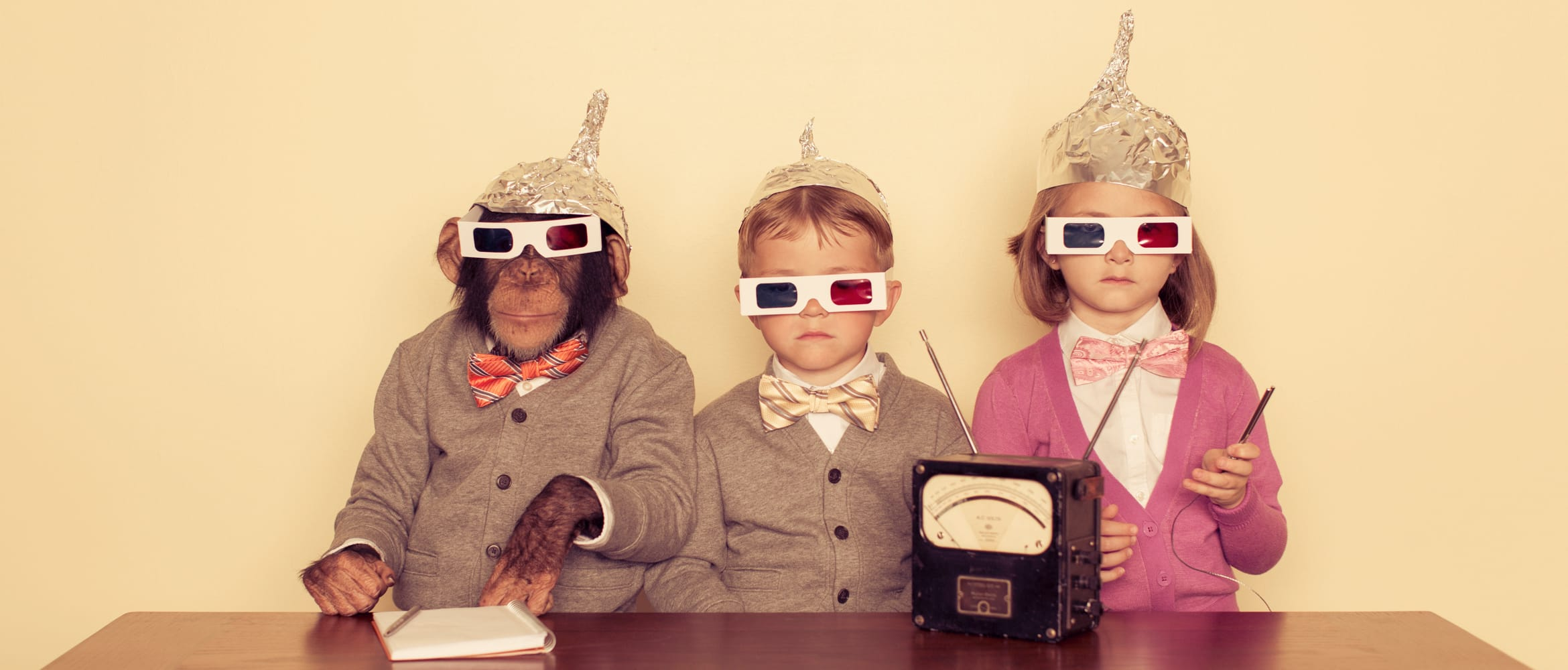 a monkey and two children wear foil hats to prevent alien communication