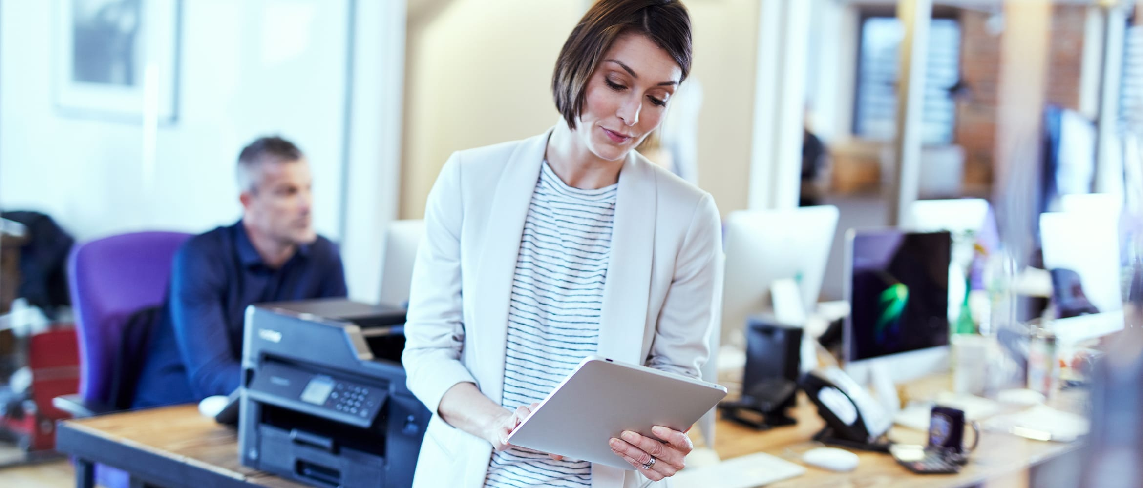 A lady printing a document from a tablet device in a small office environment