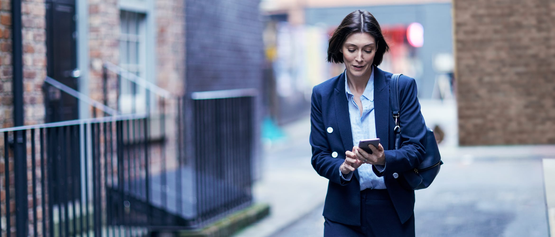A woman looking at her smartphone while walking down a street