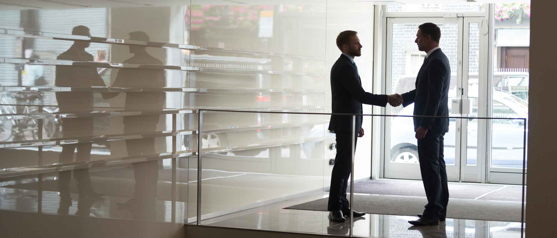 Silhouette of two businessmen shaking hands in office lobby. Male business professional executive colleagues standing near doorway of modern building, handshake.
