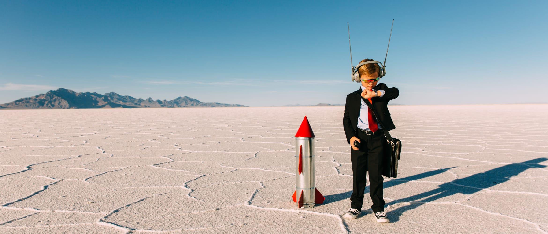 little boy in a suit prepares to launch a rocket