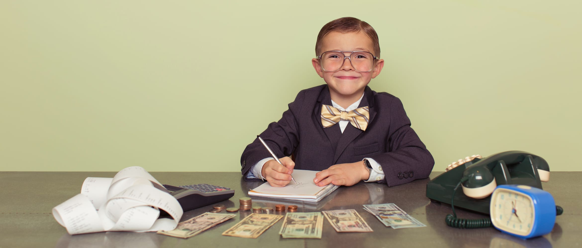 young boy businessman sits behind a desk