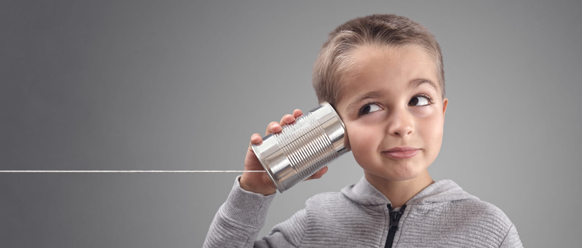 Young boy with can and string to his ear, highlighting the principles of remote working