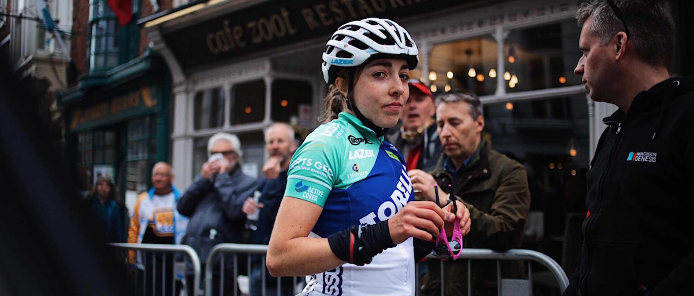 Cyclist Sophie Wright looking at the camera and holding her sunglasses in her hand