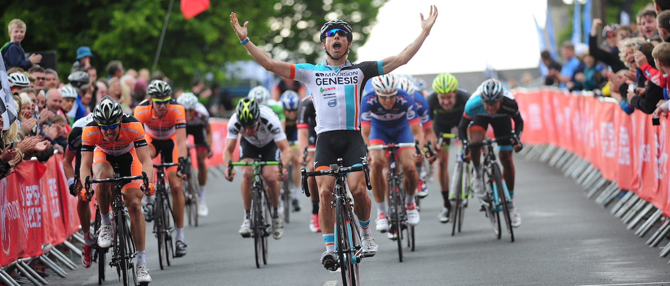 Cyclist Dean Downing with his arms in the air as he crosses the finishing line with spectators behind barriers on both sides of the road and other riders in the background