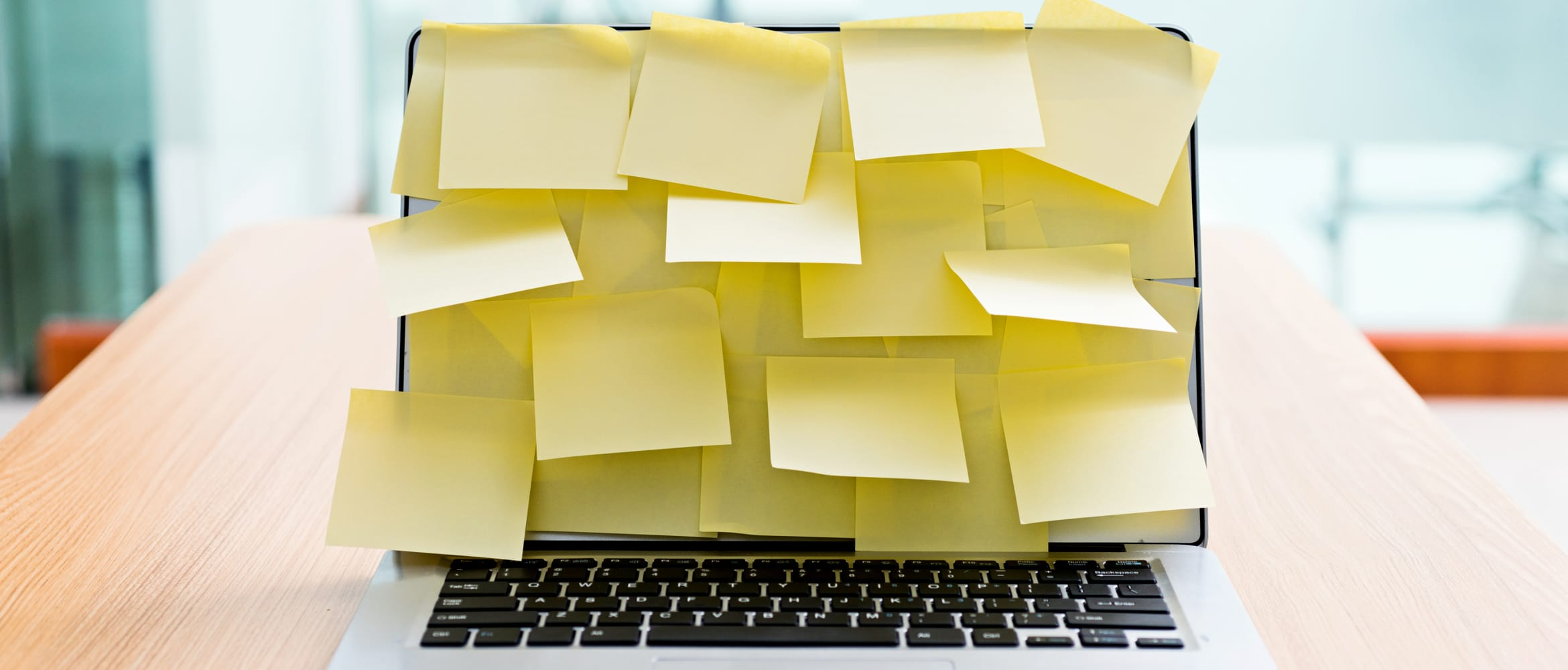 A laptop screen covered in yellow post-it notes
