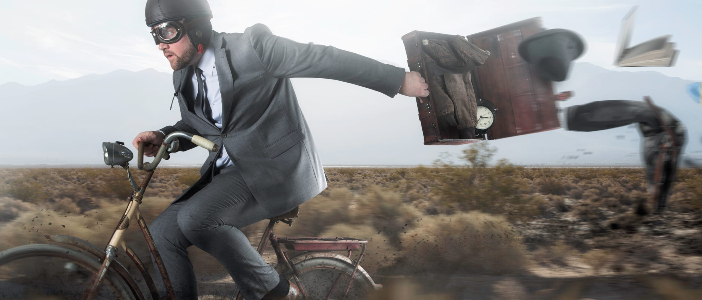 man in a suit and helmet rides a bike while his briefcase blows open
