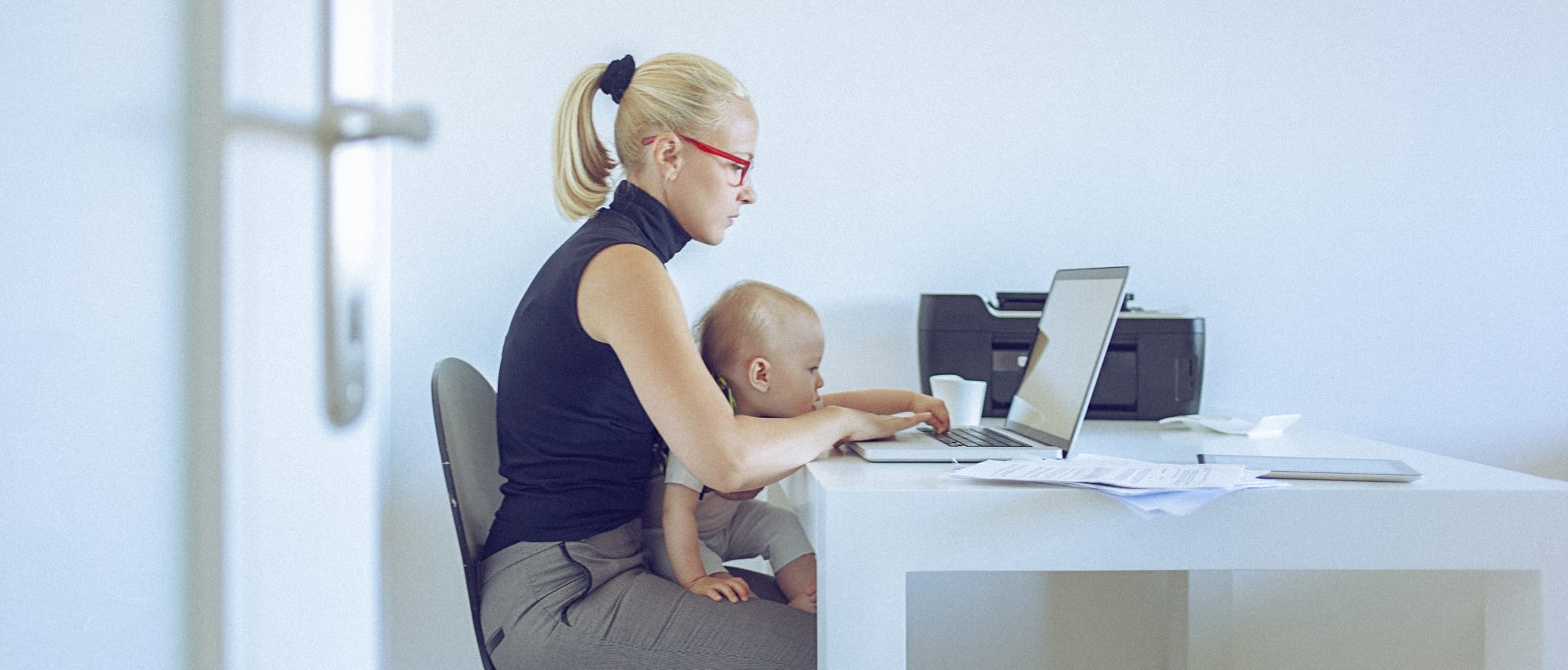 woman working from home with baby on lap