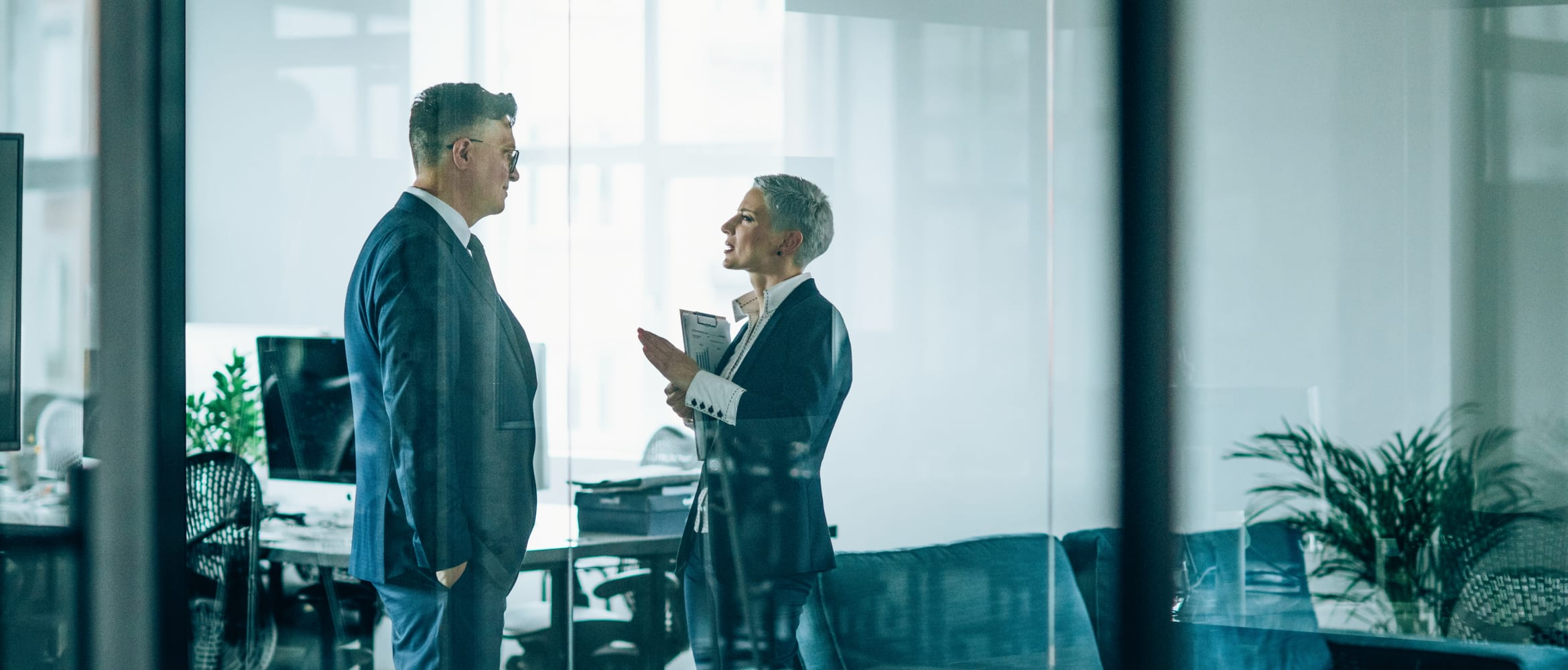 A business woman holding a clipboard and gesturing while explaining something to a business man in an office environment