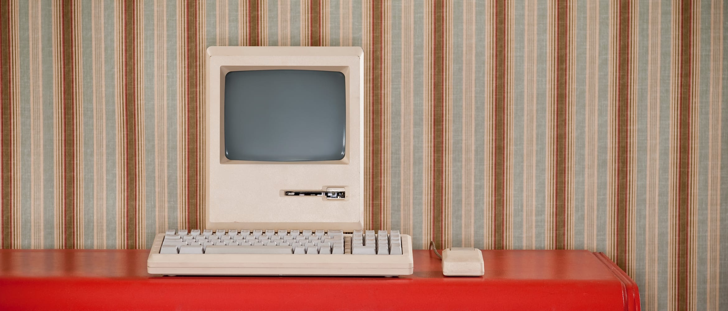an old computer sits on a desk in a retro setting