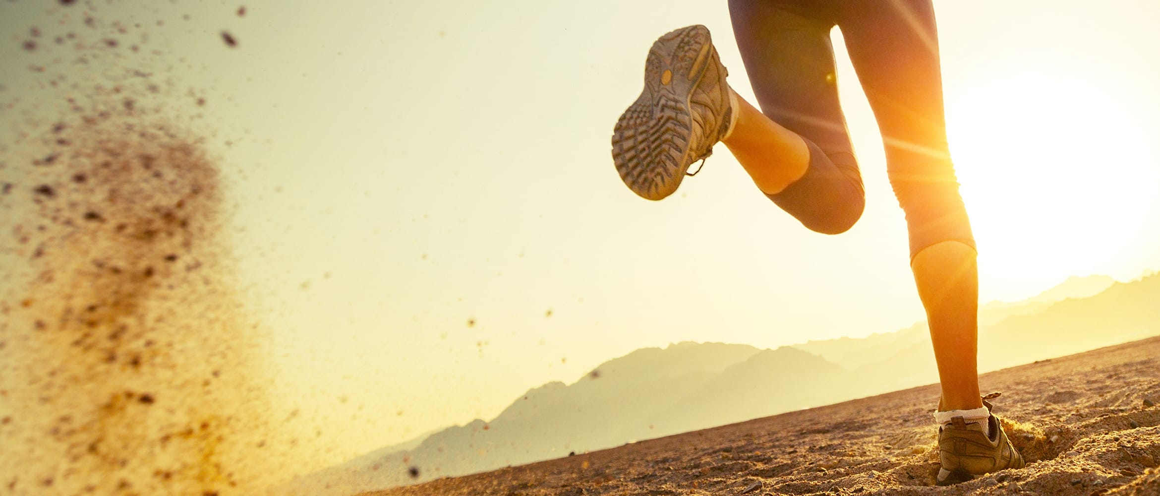 Woman kicks up dirt as she runs towards the sun