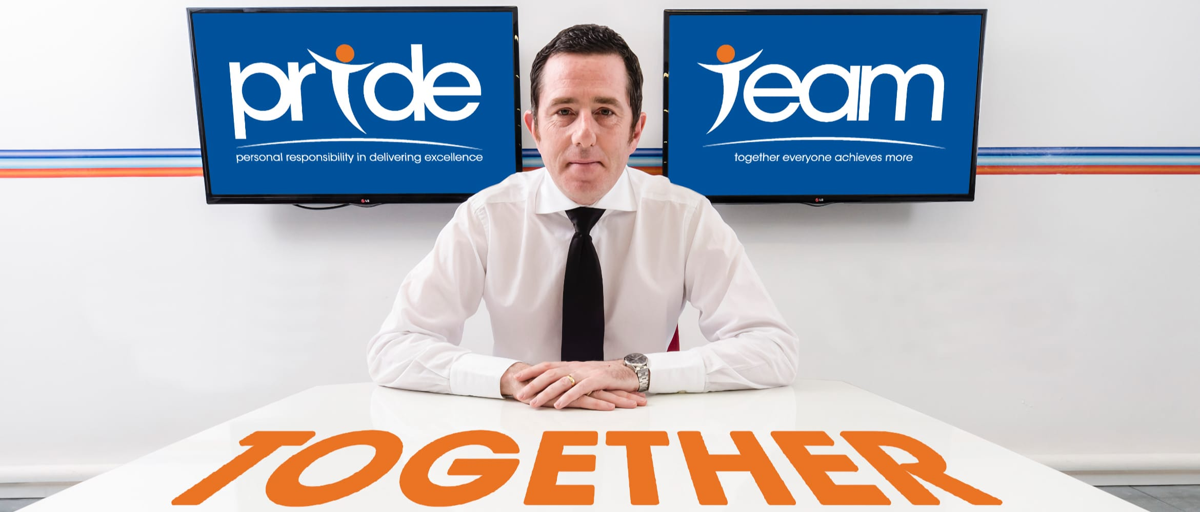Phil Jones MBE sat at a white table with 'together' written in orange in front of him and two screens behind, one displaying 'pride' and the other displaying 'team'.