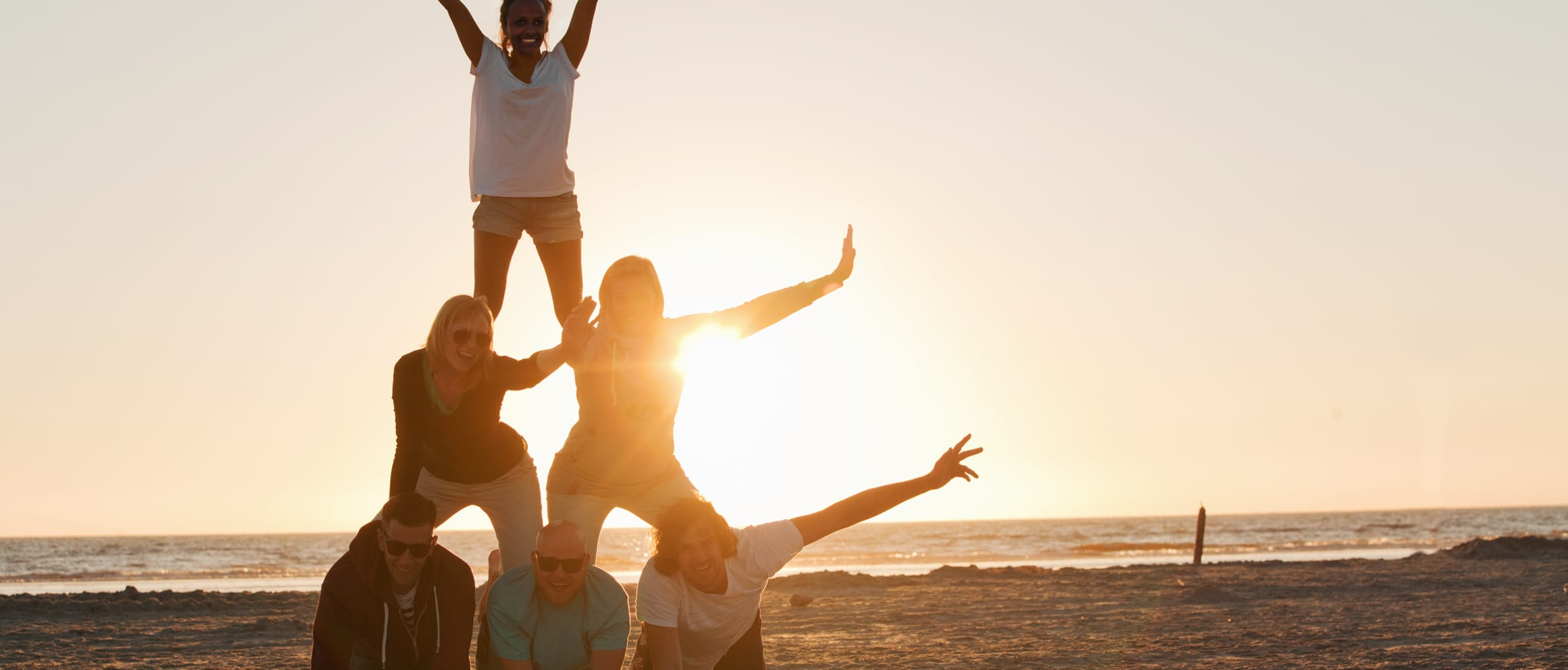 Young people making a human pyramid in the sun to illustrate Maslow's hierarchy of needs