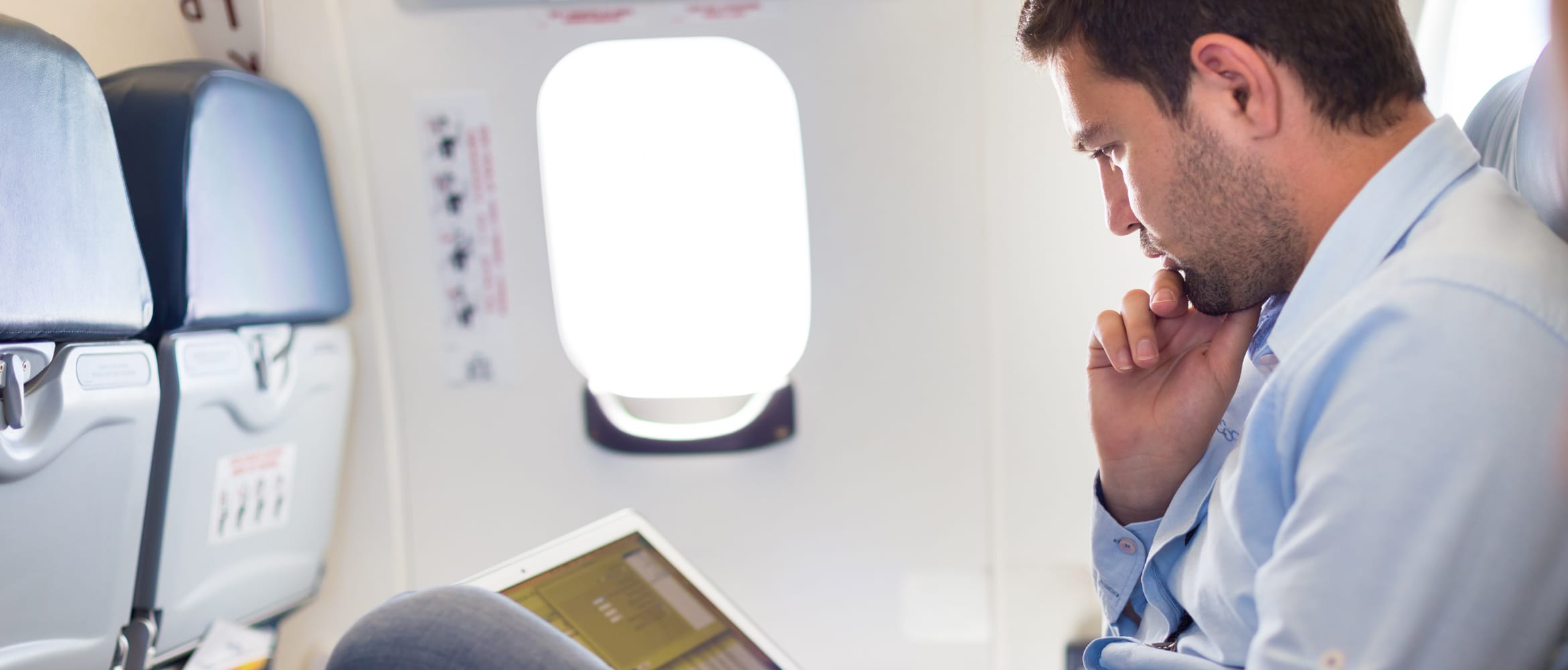 Gentleman sat on a plane using a laptop