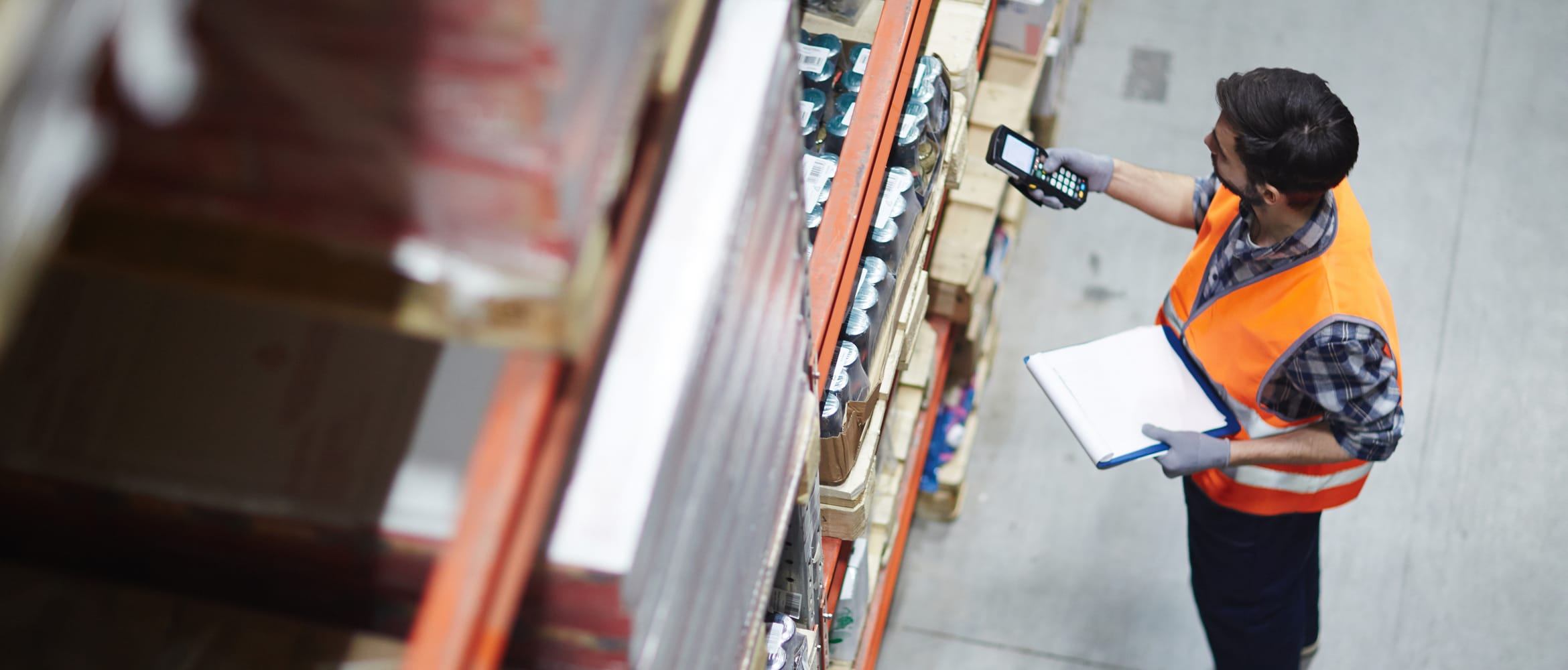 Man in a warehouse scanning with a mobile device