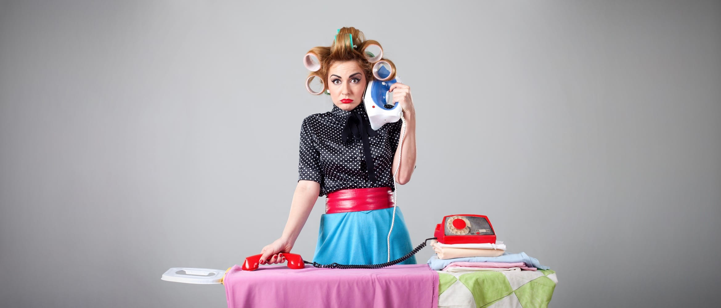 Multitasking woman puts an iron to her ear and irons a shirt with a phone to illustrate being overwhelmed
