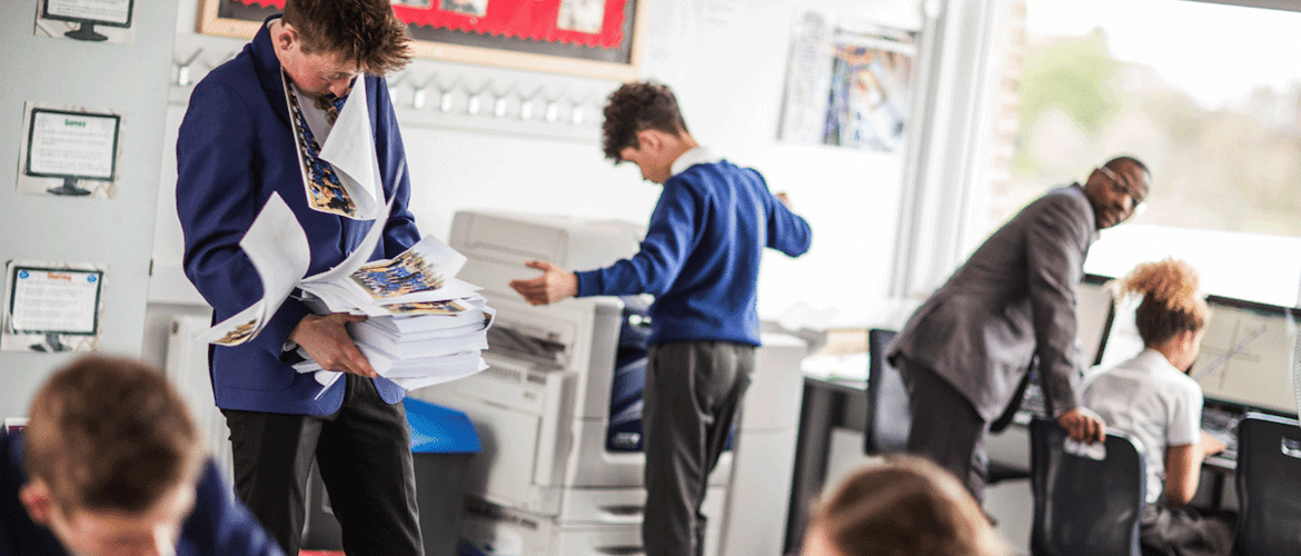 teacher looks on in dismay as students print hundreds of sheets of paper from classroom printer