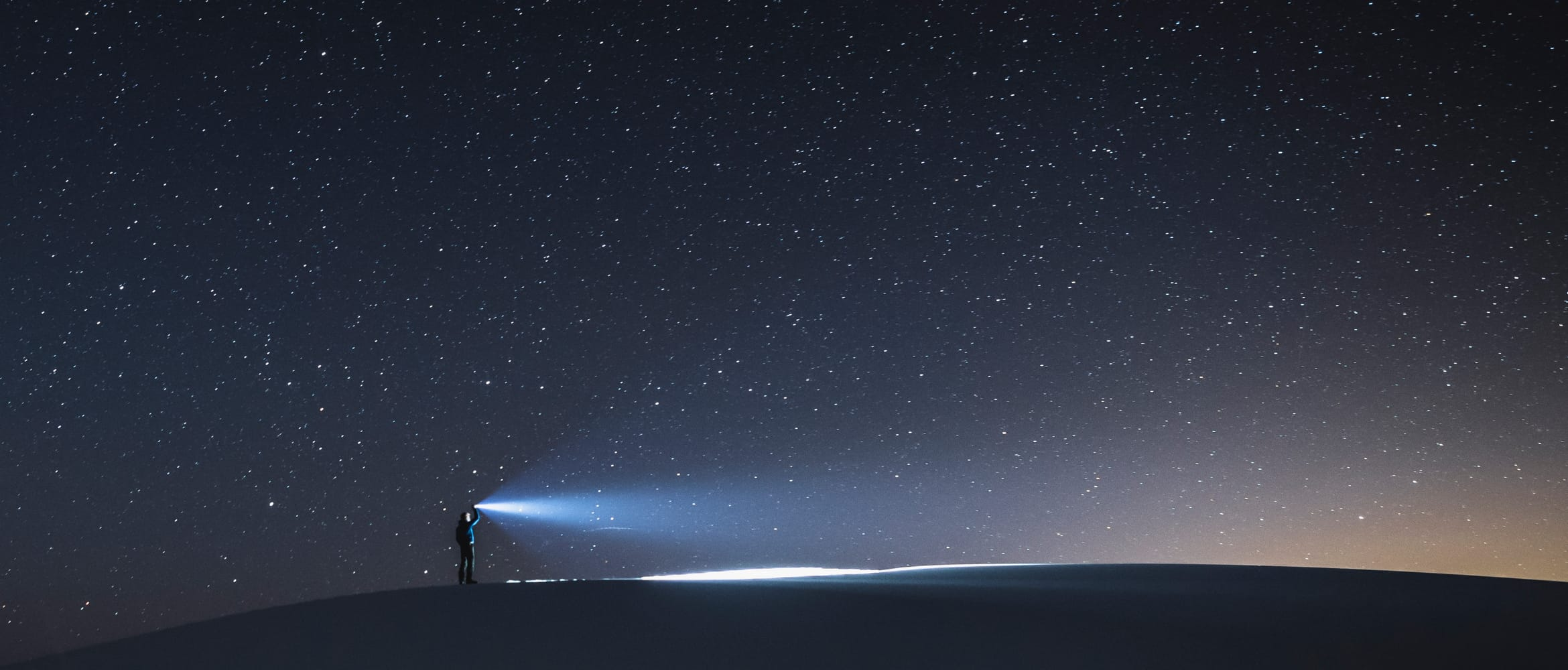 lone person shines light in the dark at night