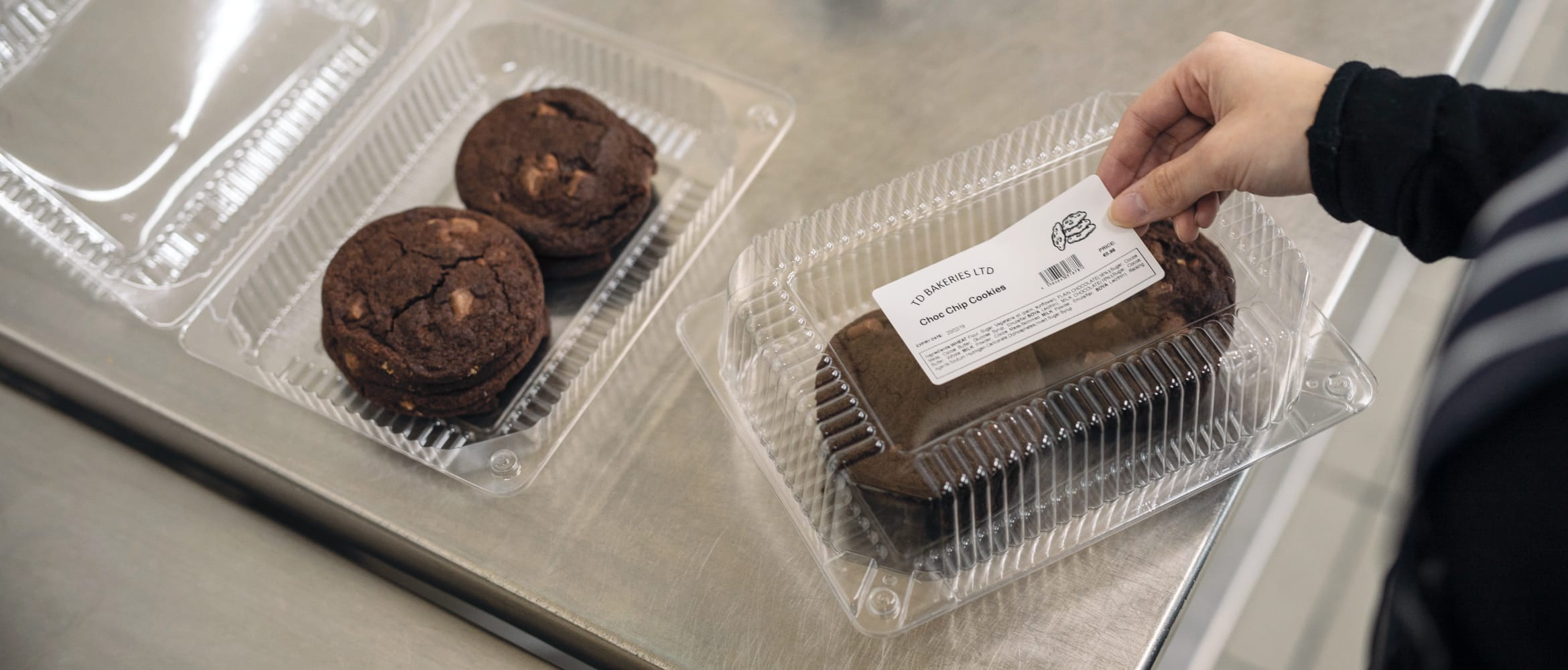 A baker applying an adhesive food description label to a clear plastic box containing choc chip cookies in a kitchen environment