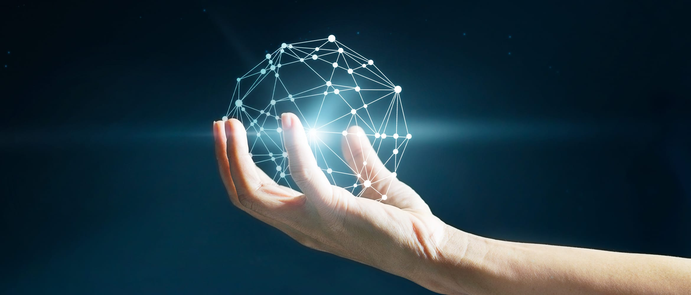 Hand holds a geometric glowing globe to illustrate the responsibility of change management, particularly within the NHS