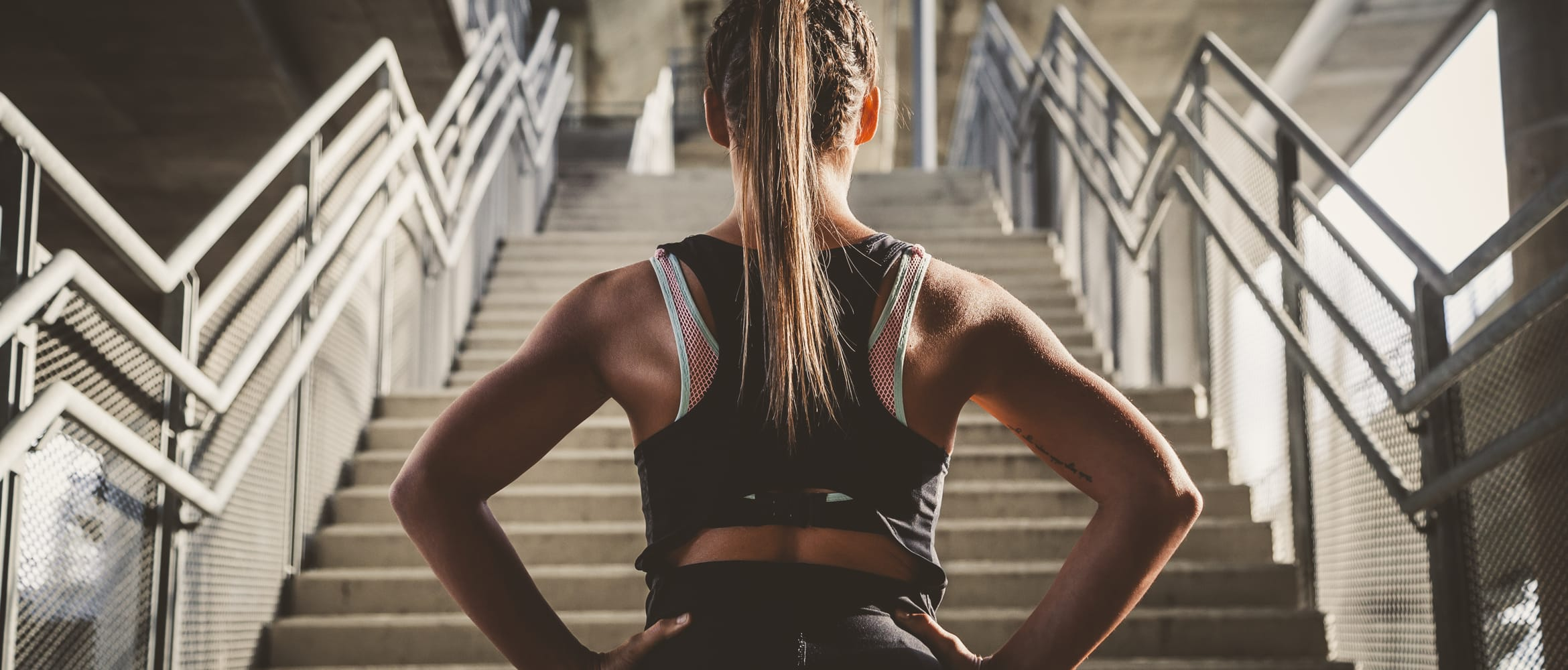 woman in gym kit prepares to run up steps
