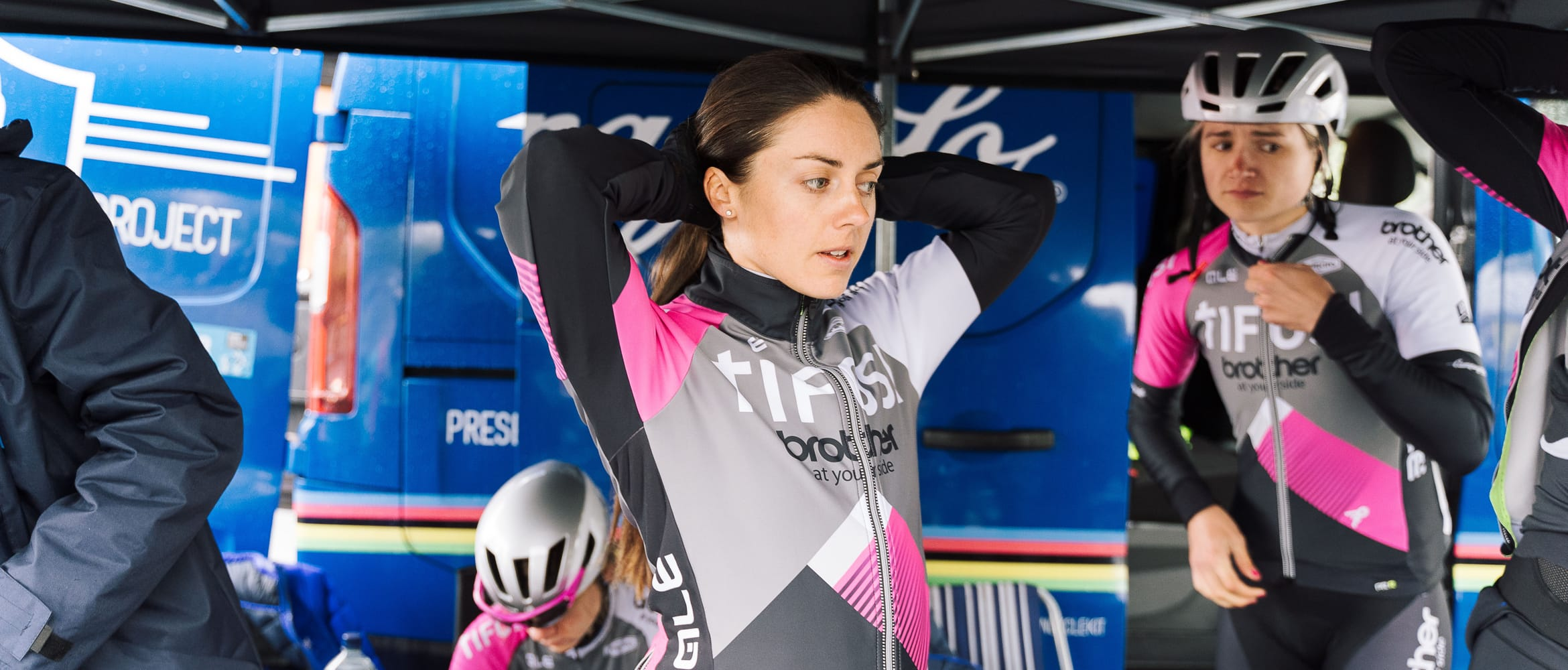 Cyclist Rebecca Durrell preparing for a race in front of a support vehicle with other team mates from the Brother UK-Tifosi p/b OnForm squad