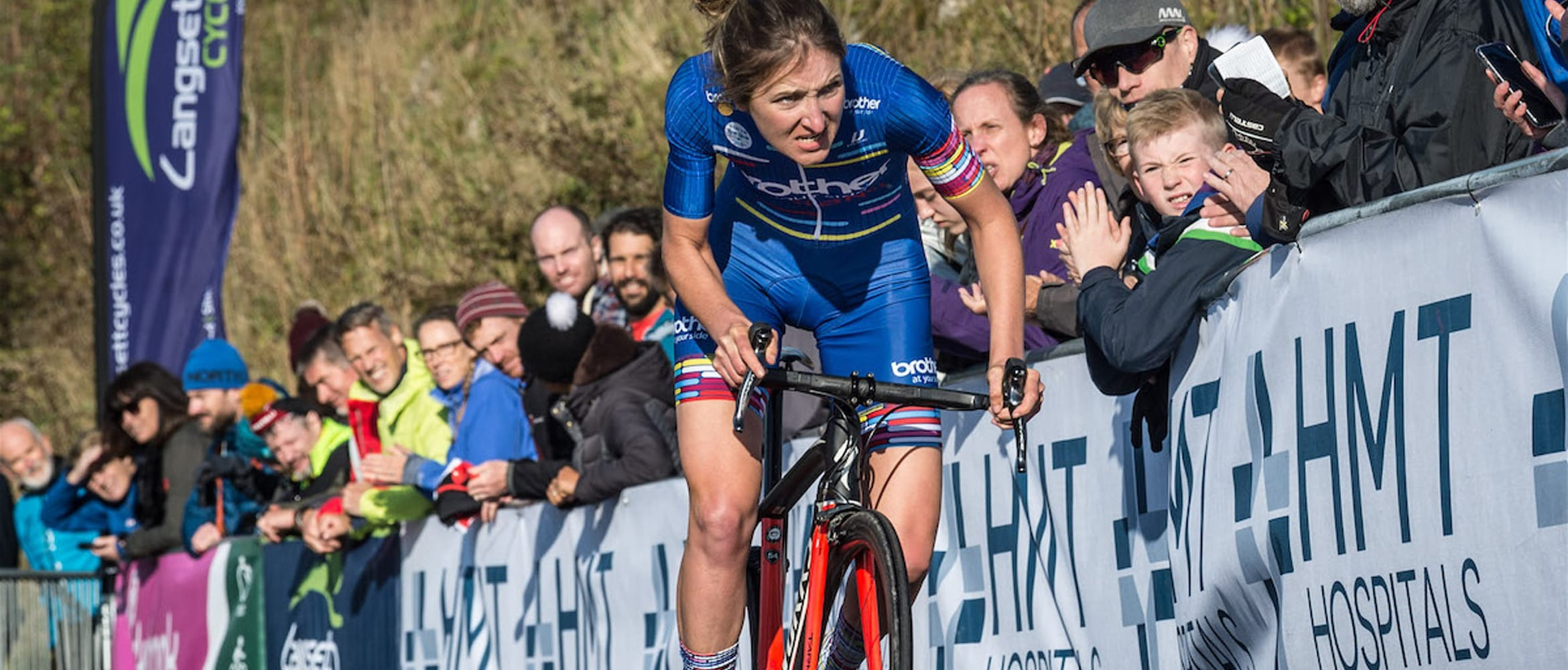 Cyclist Rebecca Richardson approaching the finish line of a hill climb with spectators cheering her on