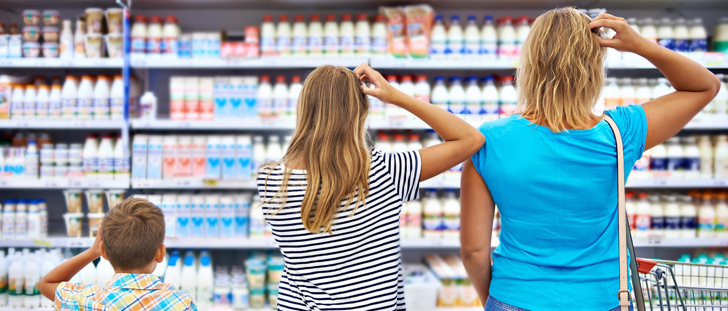 A family scratch their heads looking at a supermarket shelf to illustrate retail customer pain points