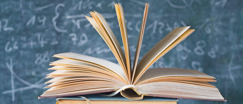 an open book in front of a blackboard
