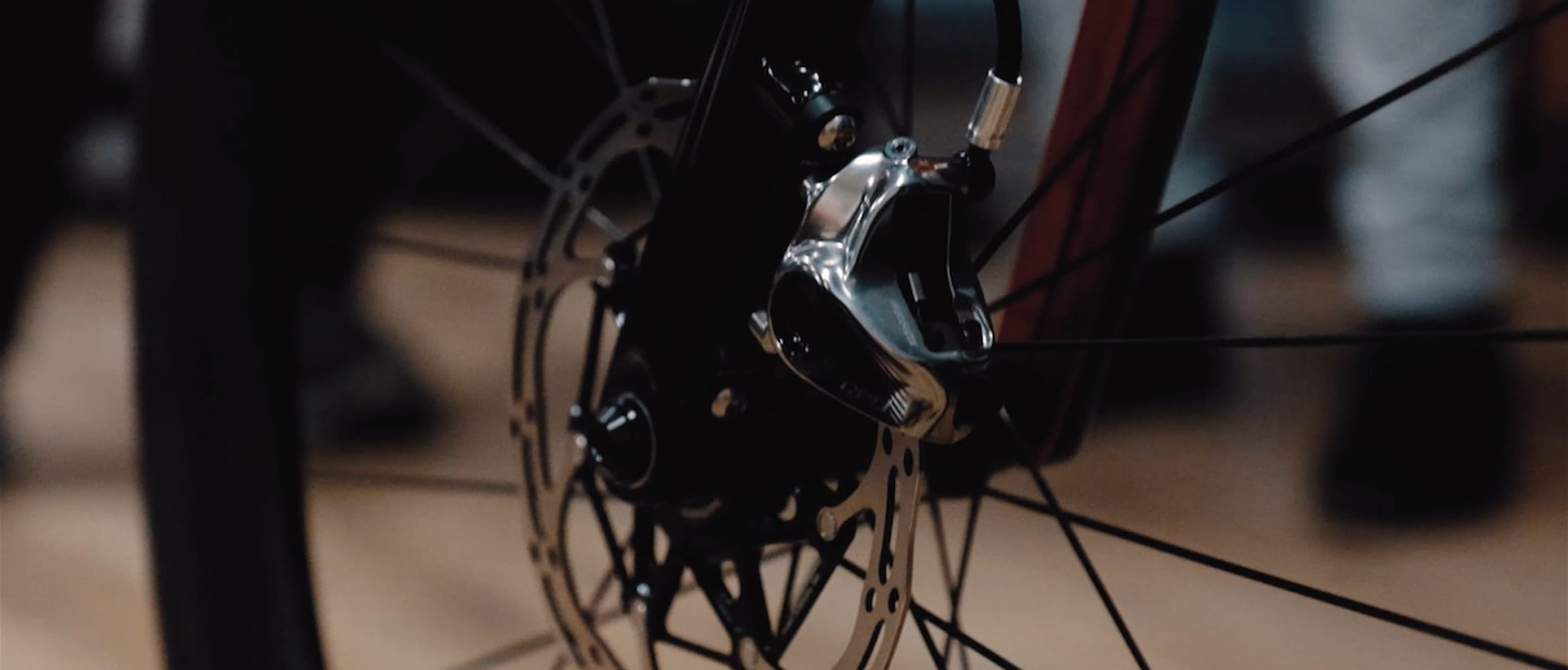 Close-up of bicycle disc brake with people's feet in the background