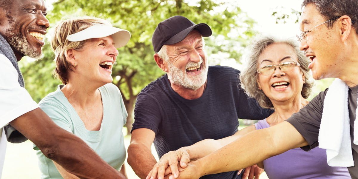 ageing people putting their hands in during a huddle