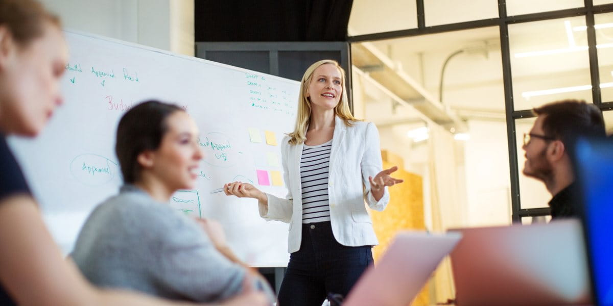 SMB business meeting being chaired by a woman in front of a whiteboard