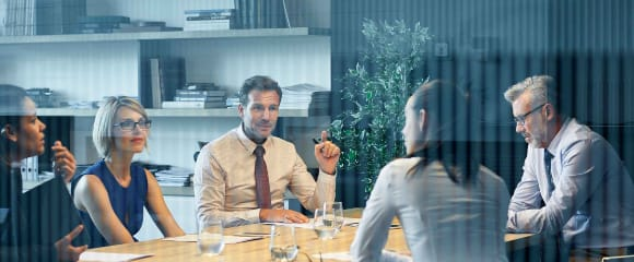 Business people communicating at desk seen through glass. Coworkers are discussing in meeting. They are sitting in office.